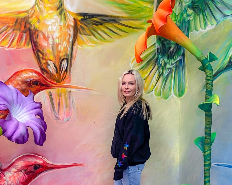 The vibrant birds were painted on the wall but the flowers were standing on the floor, giving it a 3D effect.